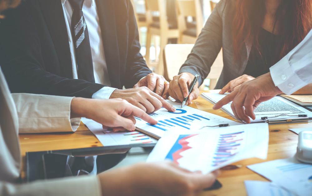 Factoring Geschäftsläute sitzen um Tisch und diskutieren über Voraussetzungen im Factoring